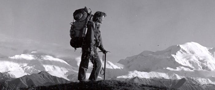 black and white image of person with pick and large mountaineering pack standing on a rocky peak with large snowy mountains in background