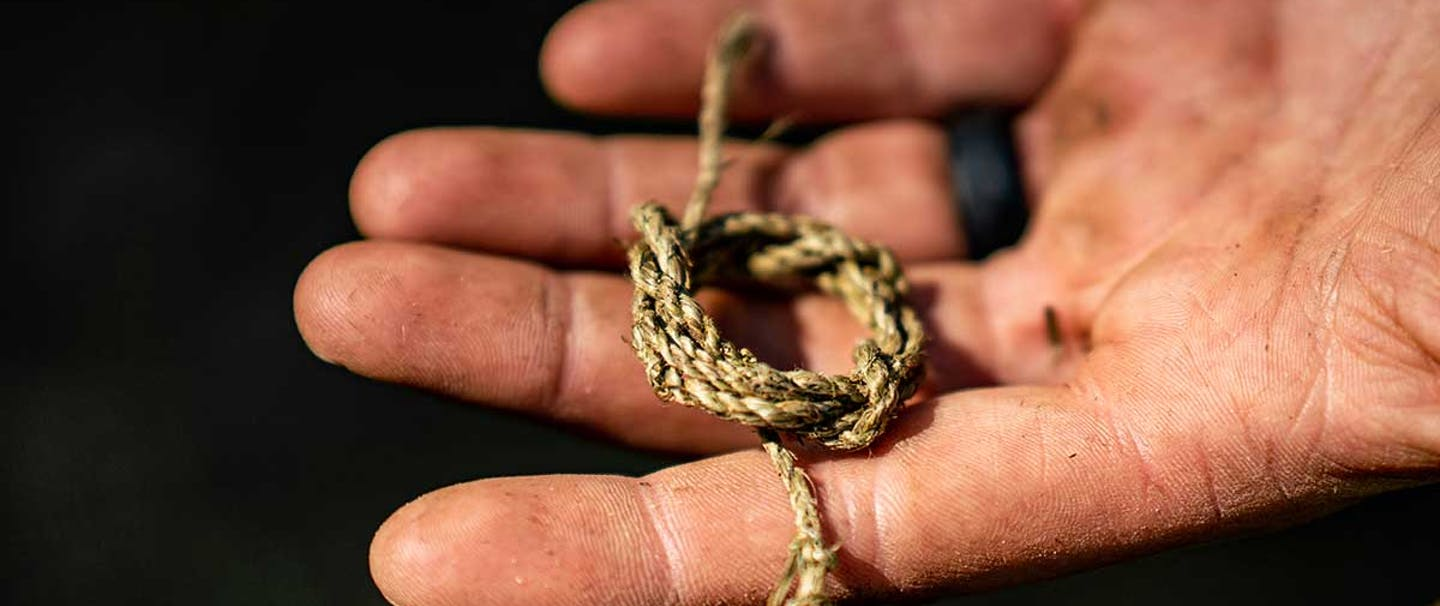 hand holding a small section of woven thin gauge rope tied in a loose knot