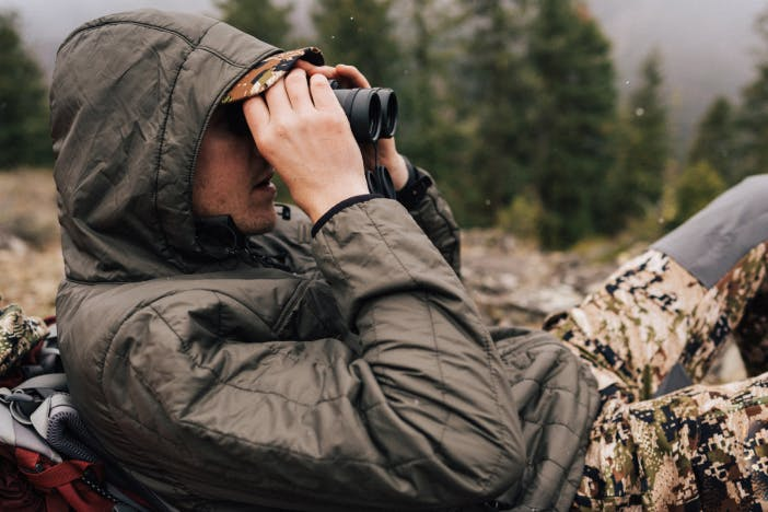 man lying with backpack under back with black coat and camouflage pants on using binoculars