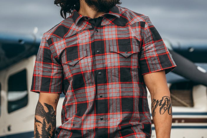 perosn with black forearm tattoos in black and red plaid shirt
