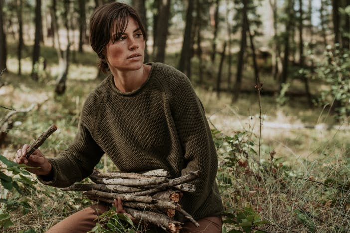 woman wearing a brown knitted sweater gathering medium sized sticks in a meadow in the woods