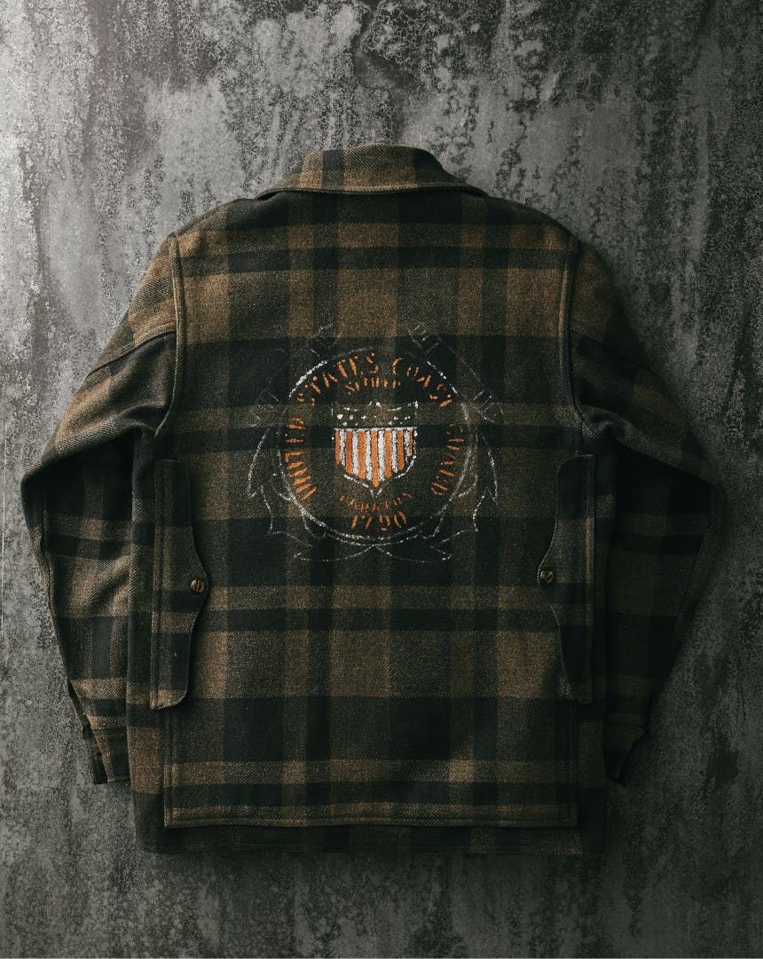 Top down view of back of US Coast Guard Jacket, olive and dark green plaid pattern with Coast Guard emblem in center of black