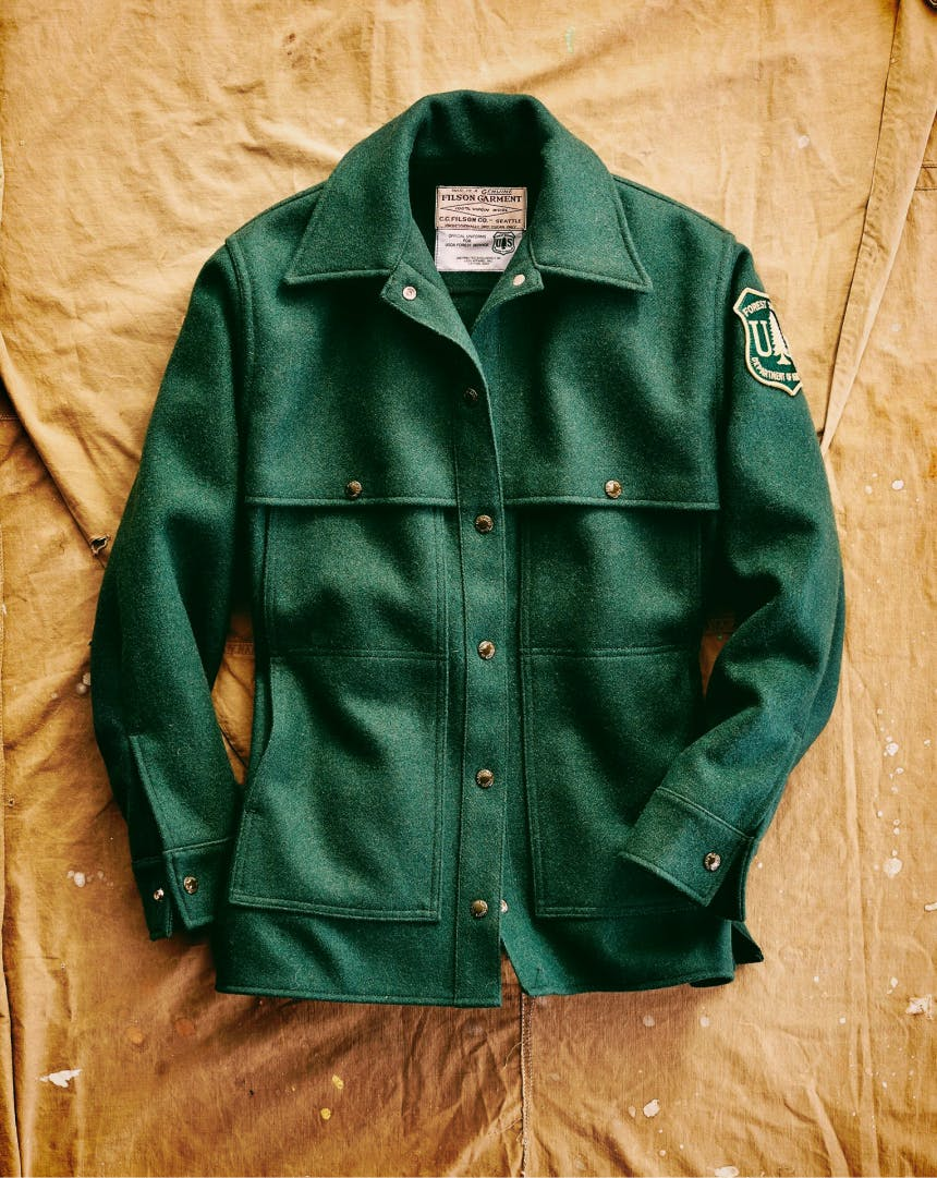 top down view of Green US Forest Service Jacket laid out on a tan cloth