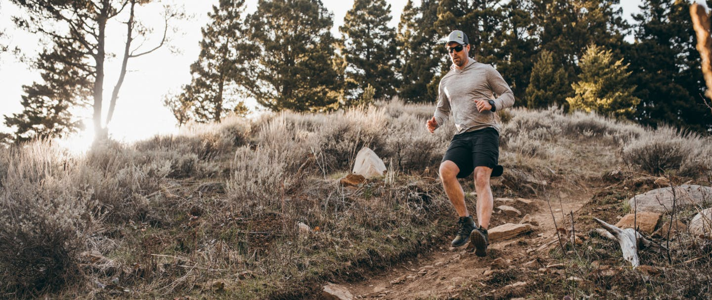 man in gray sweatshirt and black shorts running down a rocky hill in a high desert conifer forest