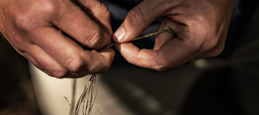 hands holding stinging nettle fibers, weaving them into a tight spiral for cordage