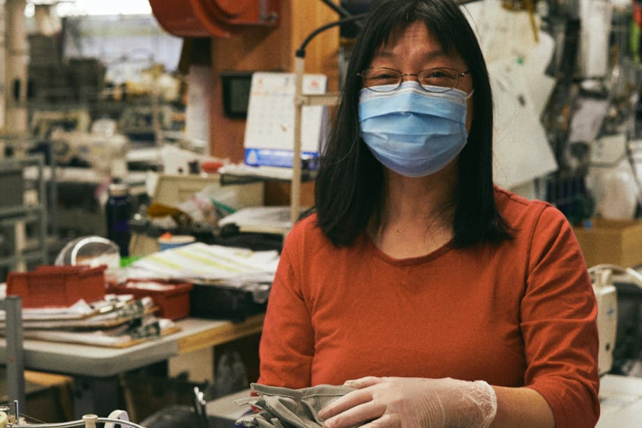 woman wearing a surgical face mask holding a stack of fabric facemasks in a textile shop