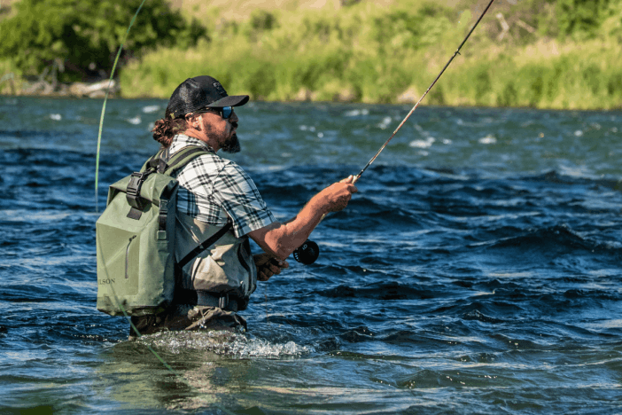 man with green filson dry bag standing in waist high water casting flyfishing rod