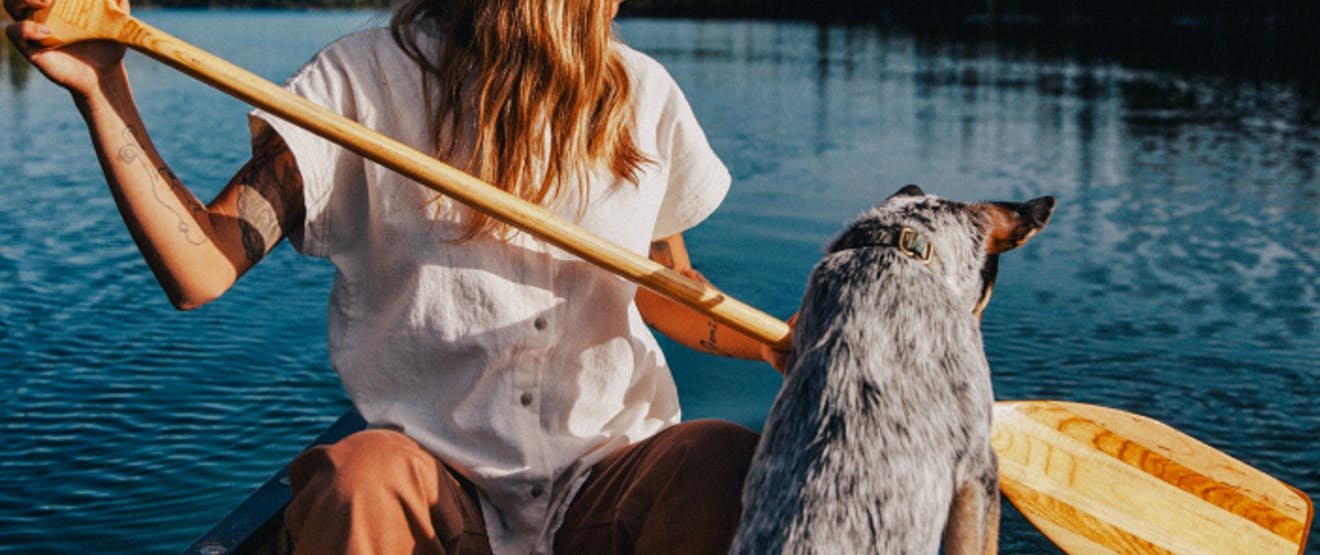 woman in white shirt holding a wooden oar sitting in a canoe next to an australian shepherd