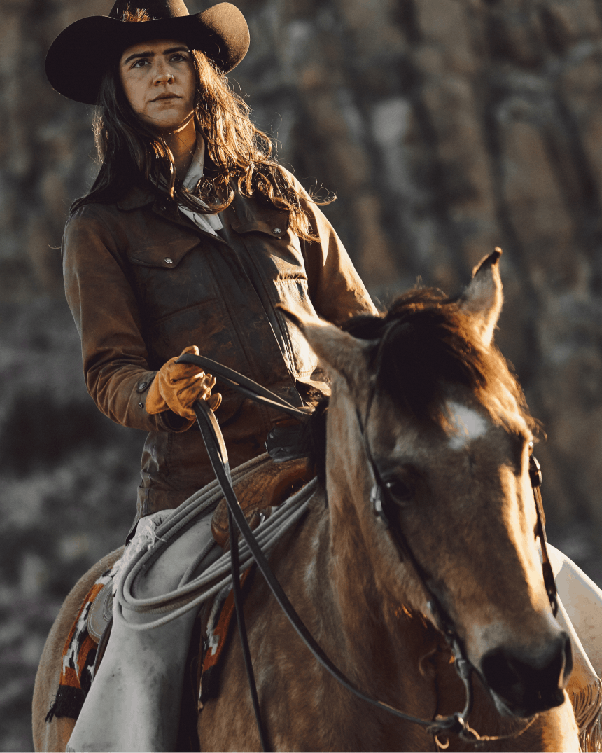 woman in black hat and brown jacket holding the reigns of a horse