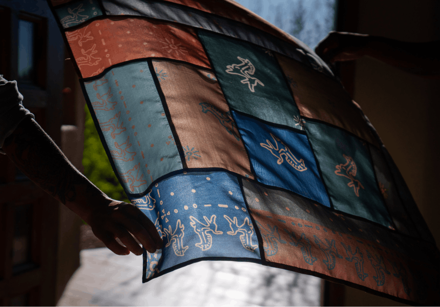 hand holding a piece of cloth with various colors and designs with sun shining through it