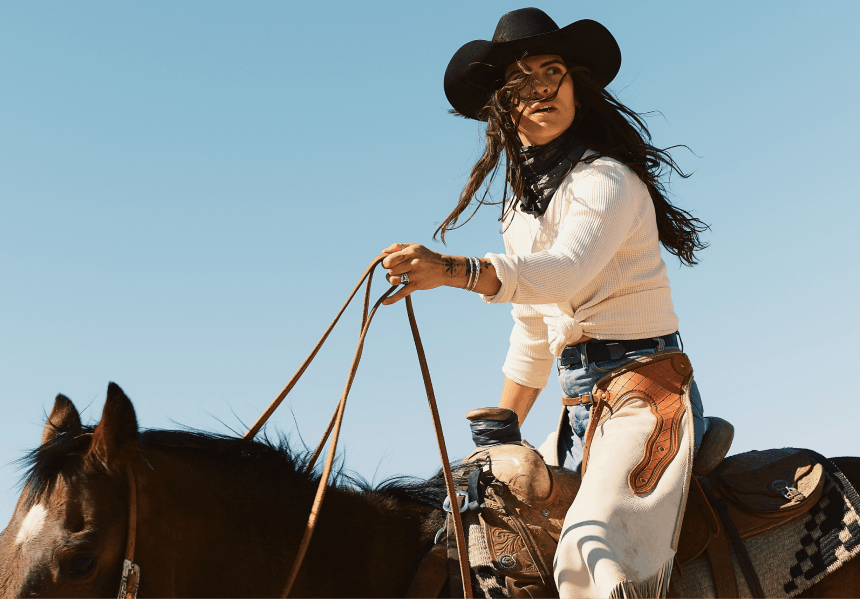 woman with black cowboy hat and white chaps and white shirt riding horse