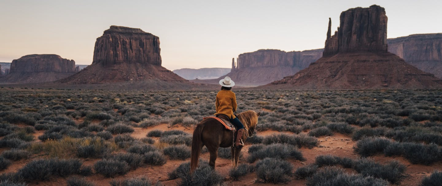 woman in burnt orange jacket and white hat on horseback looking out at the stone formations in monument valley
