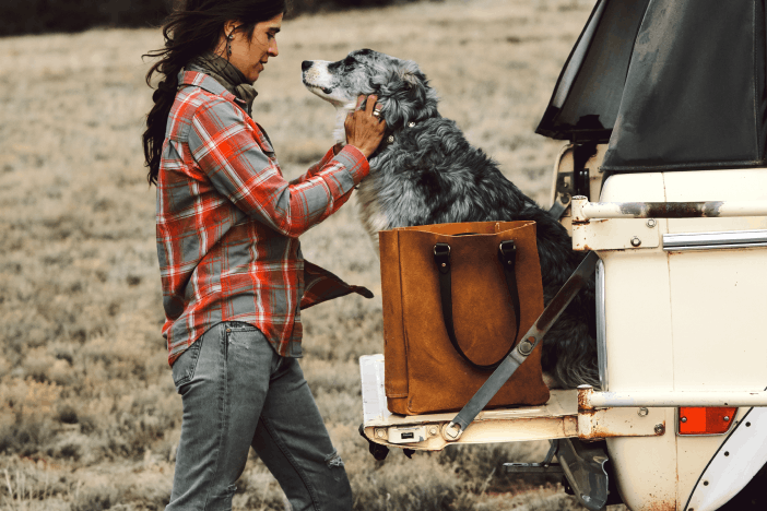 woman in red and gray plaid shirt petting a dog sitting on the tailgate of a white ford bronco next to a tan leather bag