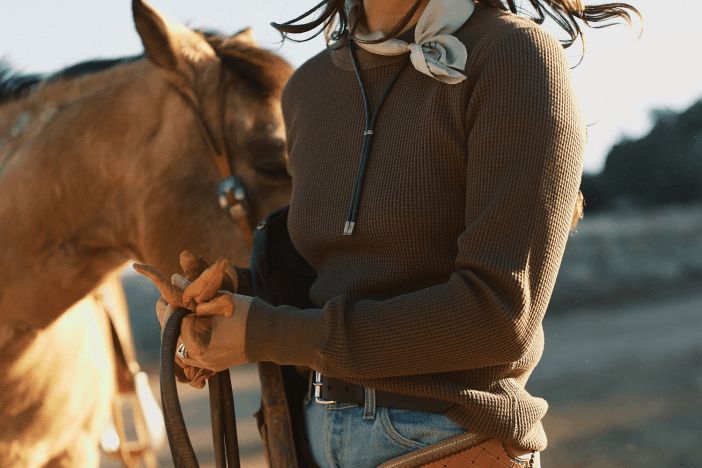 woman in brown sweater holding the reigns of a horse