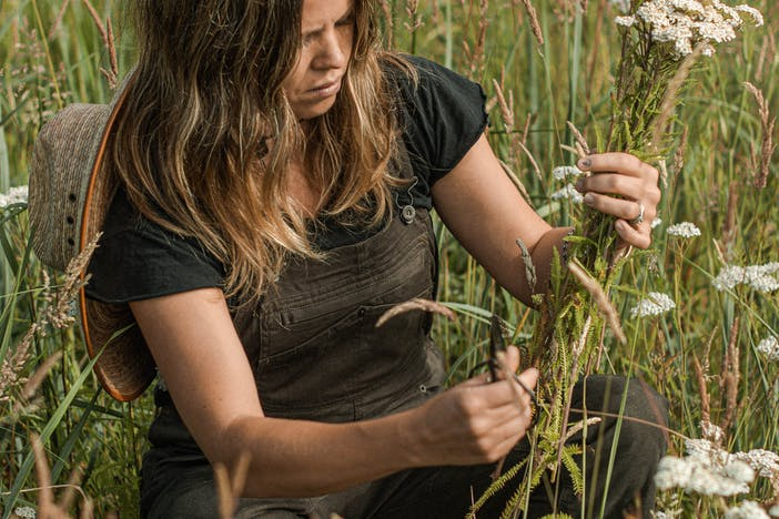 woman in black shirt squatting in a meadow holding a handful of long white flowers