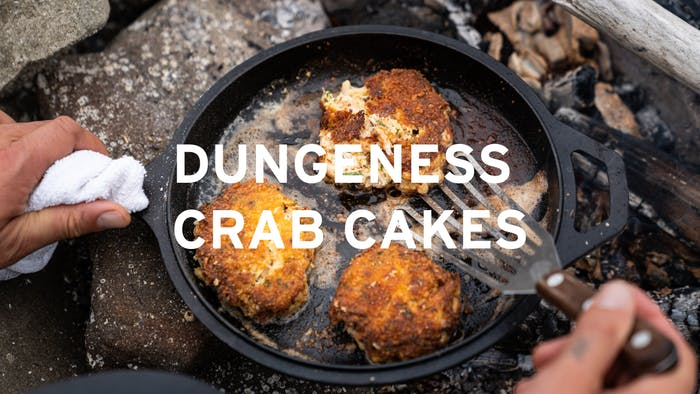 hand holding a cast iron skillet with three dungeness crab cakes over the coals of a fire central text reads