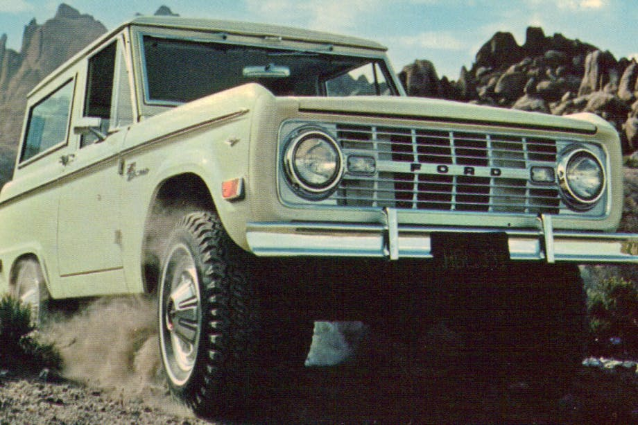 white ford bronco at a mountain pass with craggy stone cliffs in the background
