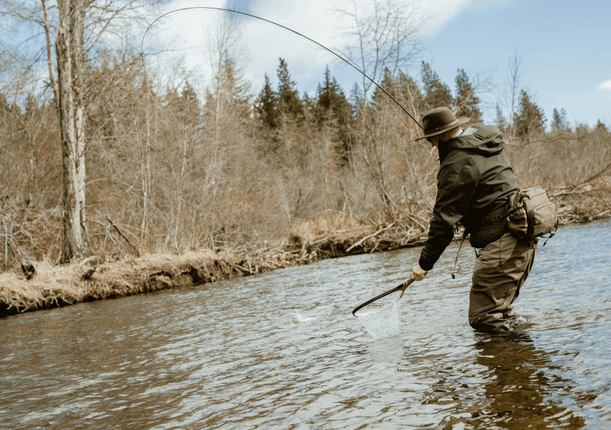 man with a fly fishing rod reeling in a fish into a fishing net
