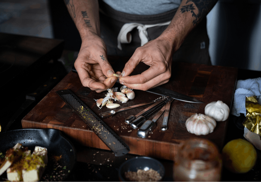 hands removing garlic peels over a wooden cutting board with measuring tools and a microplane