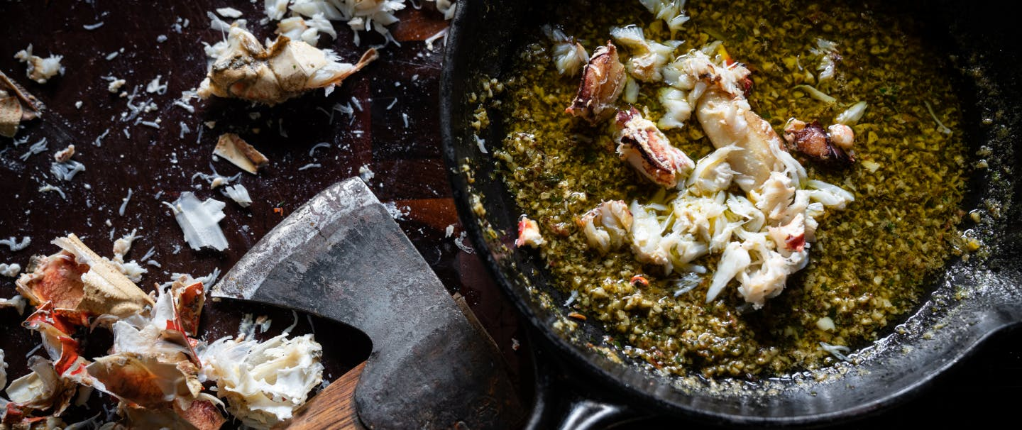 hatchet sitting next to crab shells on a cutting board, next to a cast iron skillet full of butter and herbs and crab meat