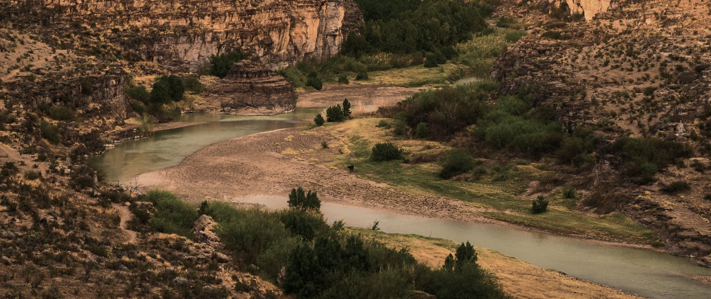 river winding its way through stone cliffs in a southwestern desert environment