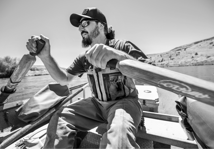 Matt Mendes sitting in a row boat holding the oars wearing waders and sunglasses and a black hat