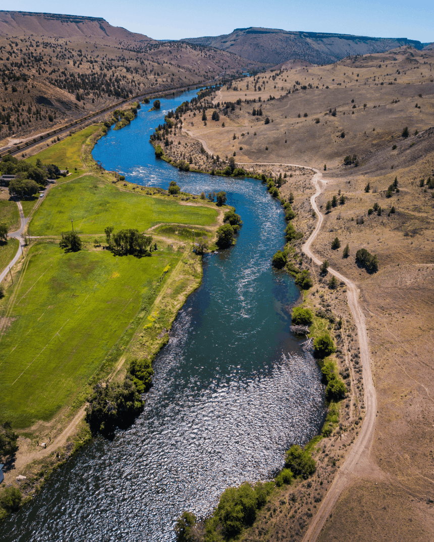 an aquamarine blue river snaking between a brown barren field on one side and a lush green field on the other