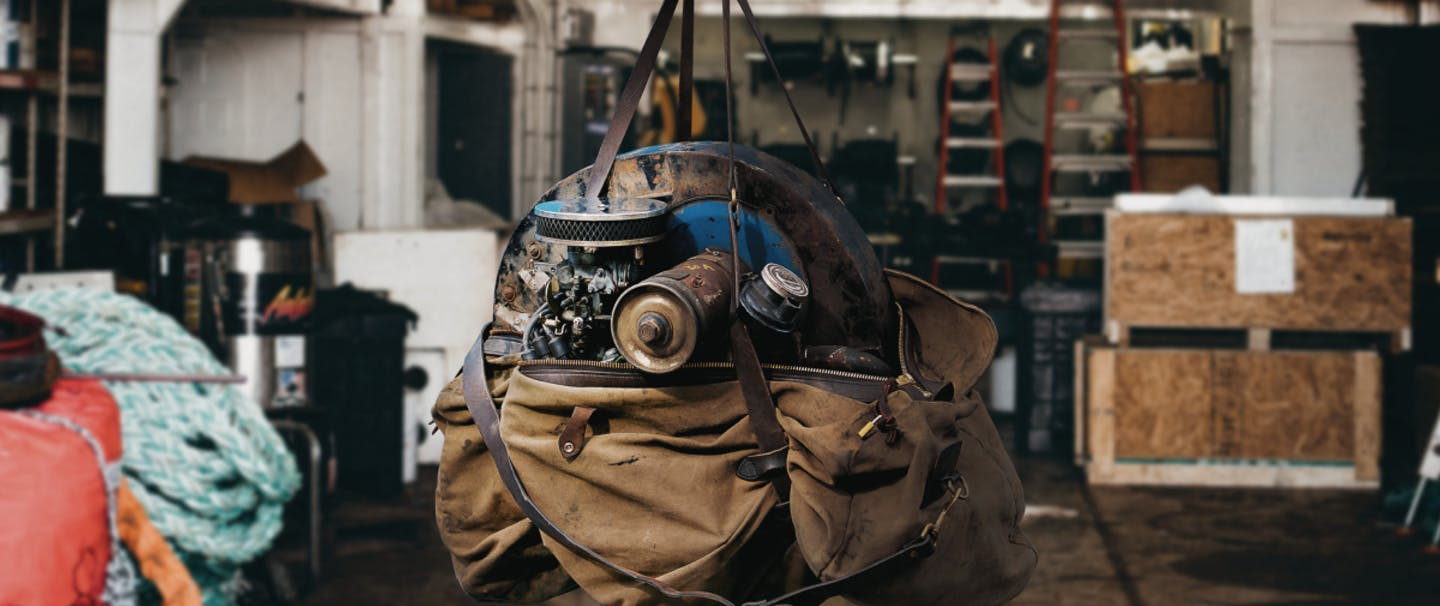 machine parts in a tan filson duffel bag hanging from a hook in the middle of a shop