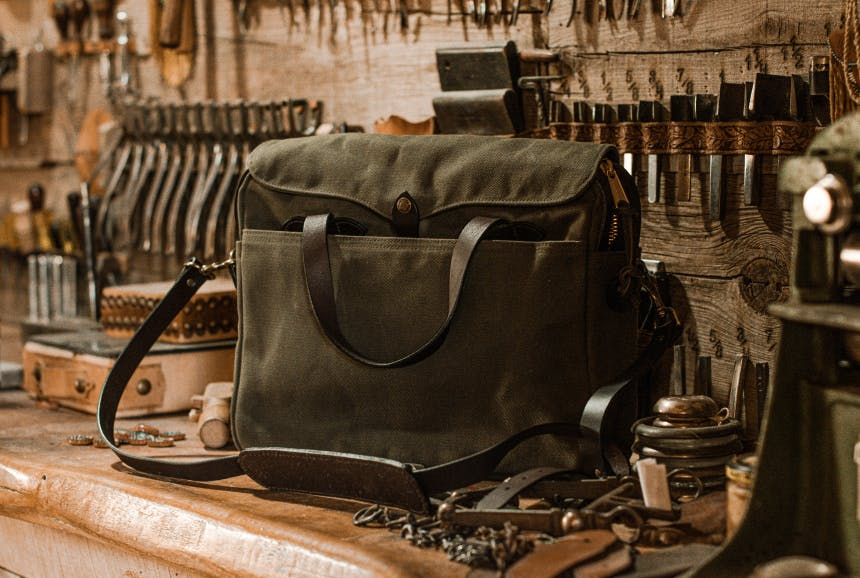 olive green filson brief case on workshop bench with many tools hanging on the wall