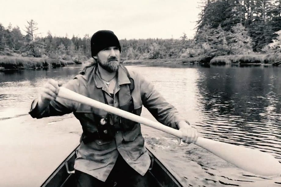 black and white image of man with a black beanie in a canoe holding a wooden oar in a boat on a river lined by pine trees