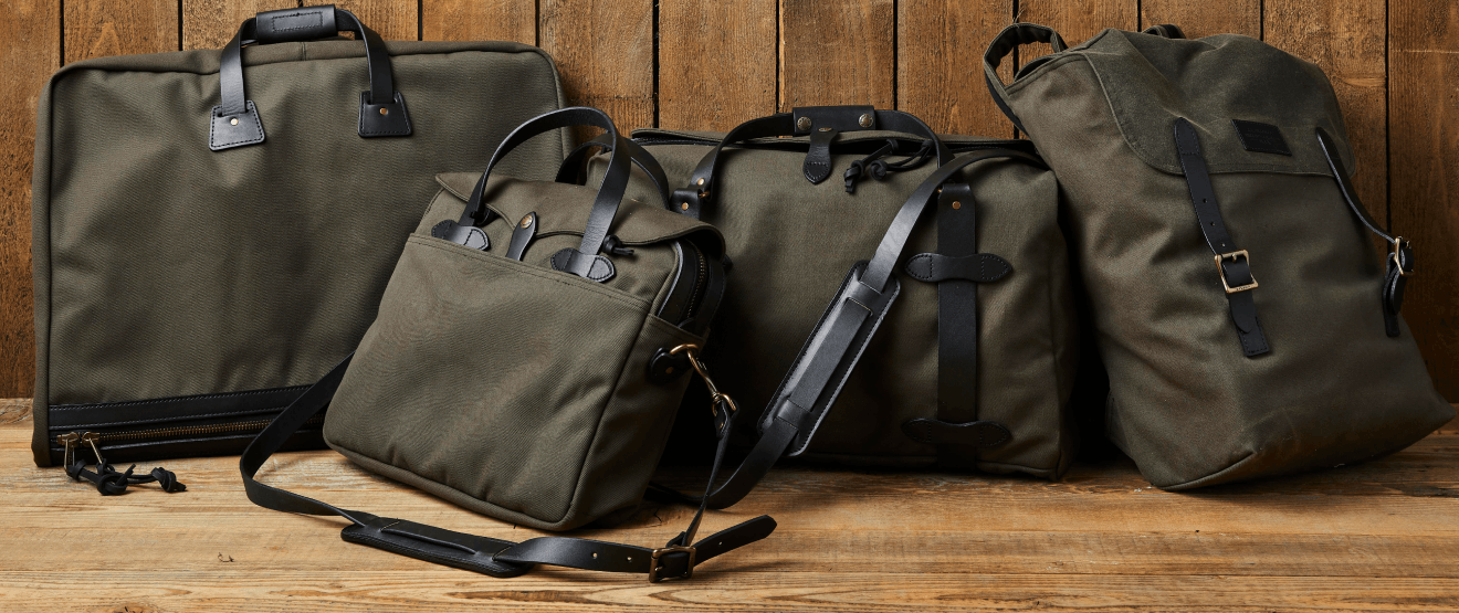 green filson bags lying next to a wooden wall