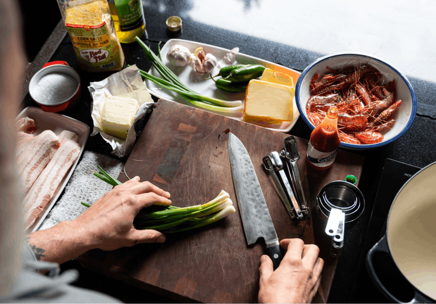 hands holding a knife and scallions with mise en place for shrimp and grits behind the cutting board