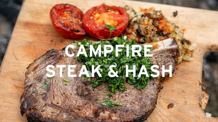 bone in steak with diced herbs, roasted halved tomato and potato hash on a wooden cutting board center text