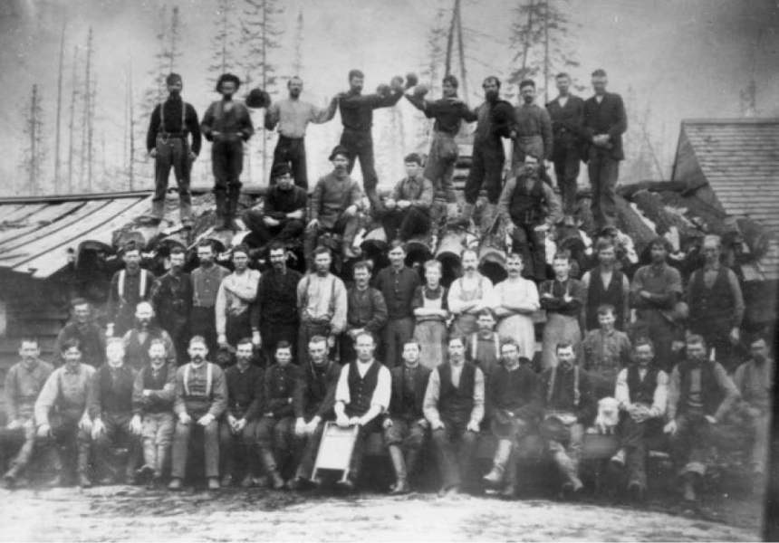black and white image of large group of loggers a group standing on a roof of a building in a logging camp