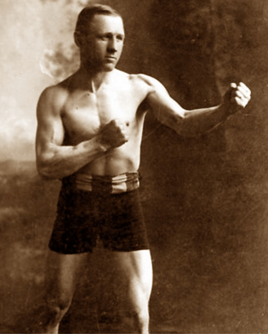 black and white portrait of a muscular boxer in antiquated boxing shorts flexing and making two fists