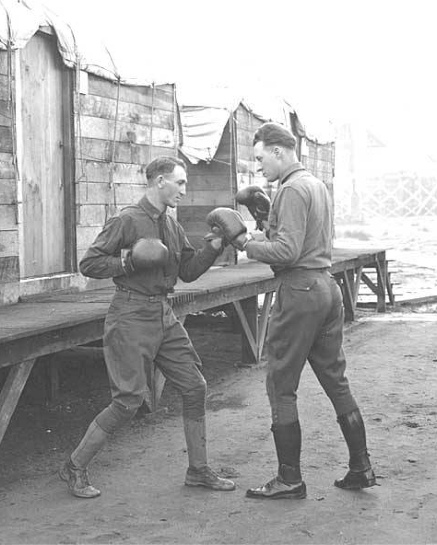 black and white image of two men doing a boxing training routine in a logging camp