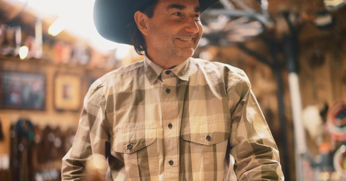 man in a dark cowboy hat wearing a white and brown shirt