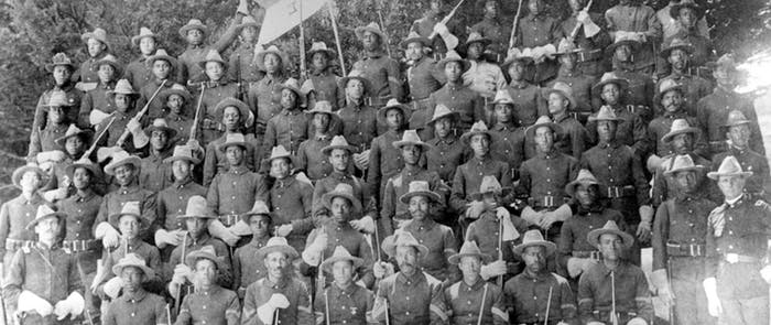 old black and white image of large group of people in dark uniforms with rifles and hats standing posing for a group picture