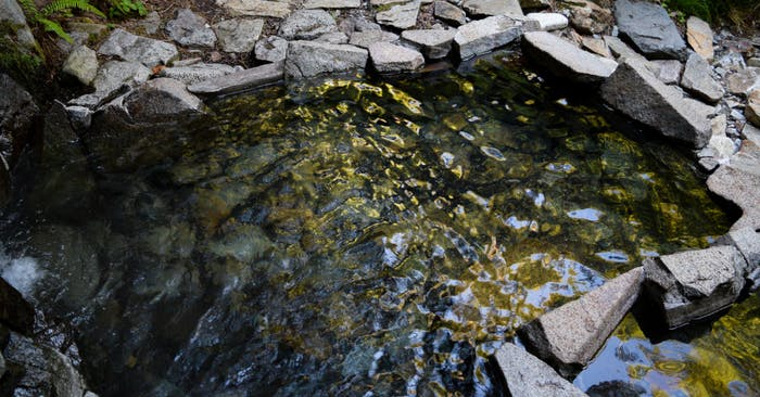 a shimmering pool of water lined by angular rock slabs
