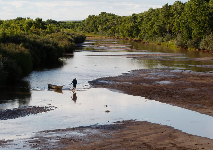 person dragging a canoe out of a river onto a more shallow water at a muddy bank lined by trees