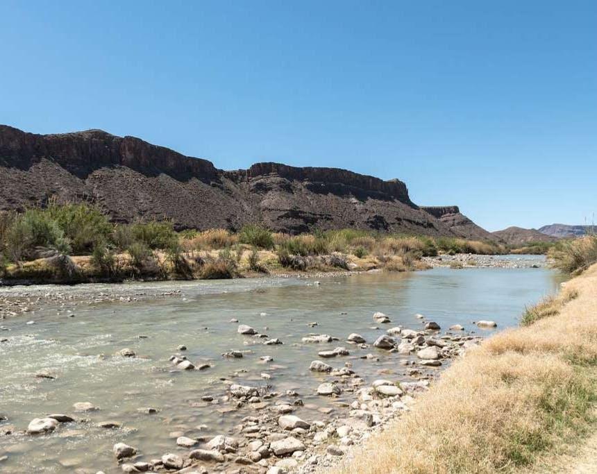 river running through a desert grassland with a dark stone mesa