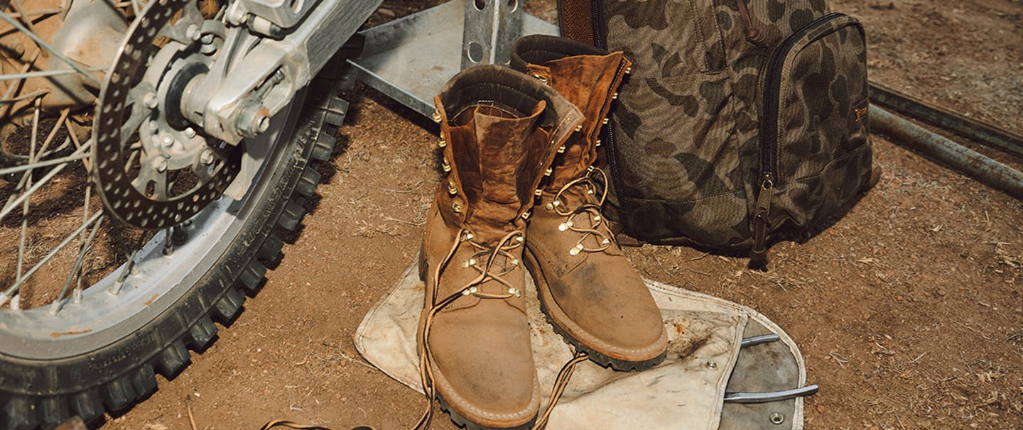 boots set on a white tool pouch next to a camouflage backpack and motorcycle