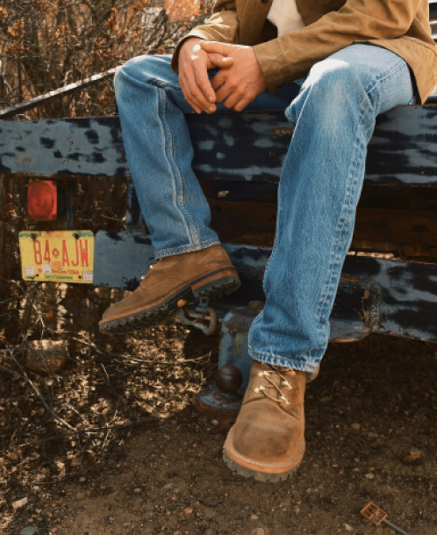 person in blue jeans and brown boots sitting on the tailgate of a truck