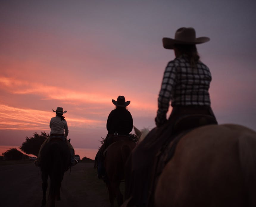 three women in cowboy hats riding horses in silhouette riding off into the sunset