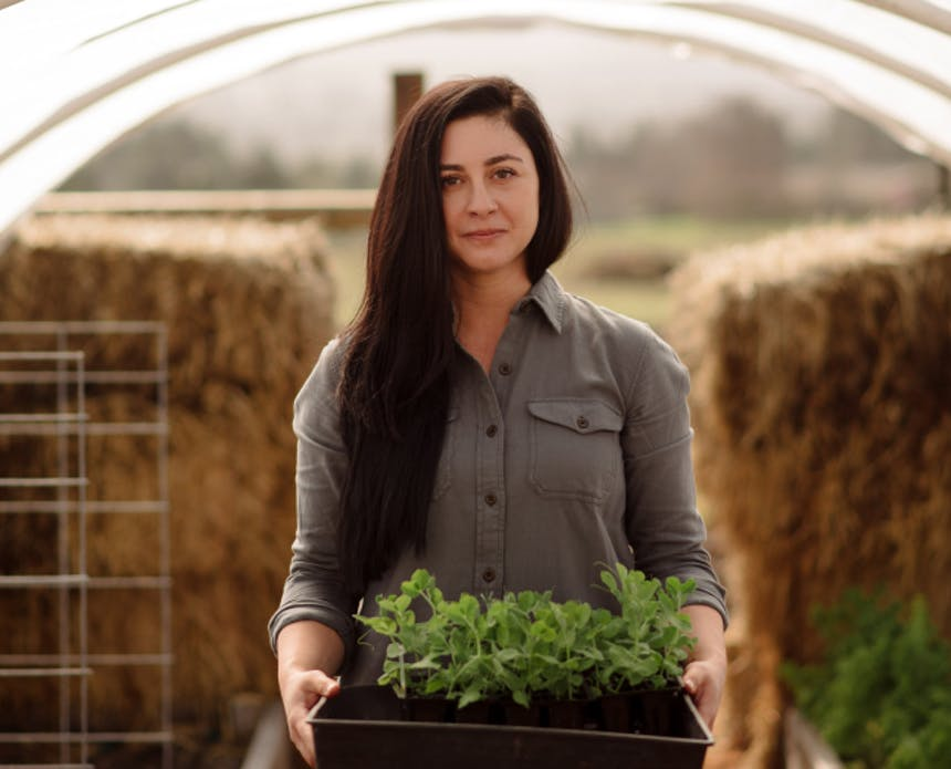 woman with long dark brown hair wearing a gray shirt holding a planter box with green herbs