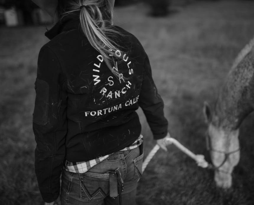woman in a jacket with wild souls logo on the back leading a horse by it's reigns