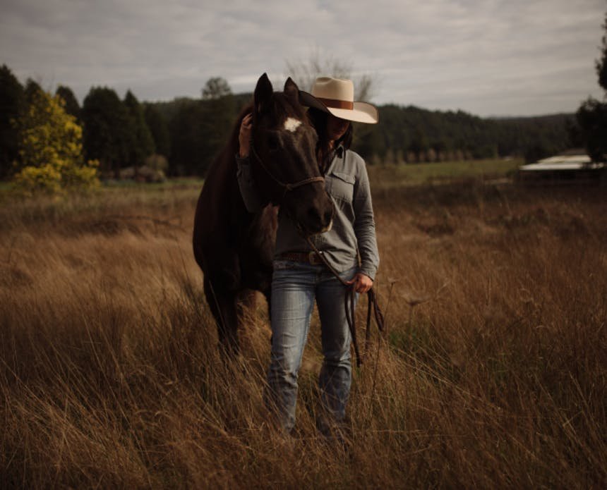 woman in white cowboy hat and gray jacket holding a horse around its neck standing in a grassy clearing
