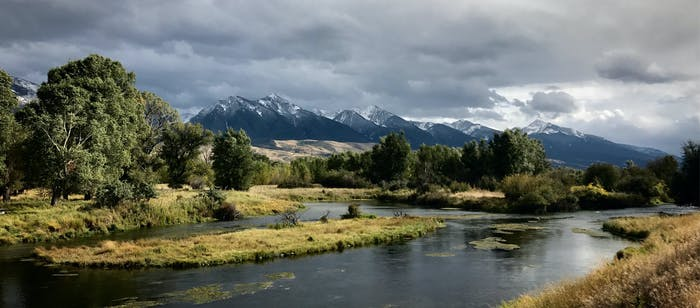river meanders in foreground with bucolic meadow and snow capped mountains in background