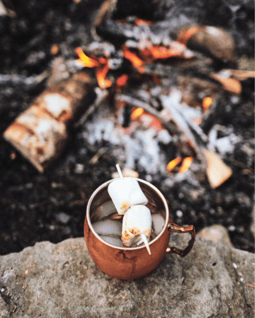 melted marshmallows stuck through with a wood skewer balanced over the lip of a copper mug