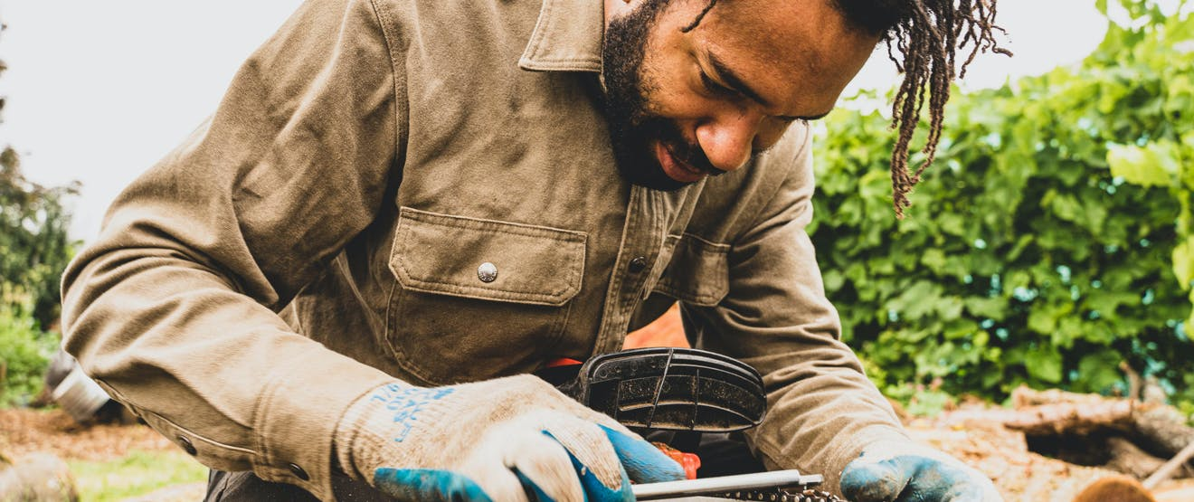 man working on a chainsaw chain while wearing cut resistant gloves in an outdoor area